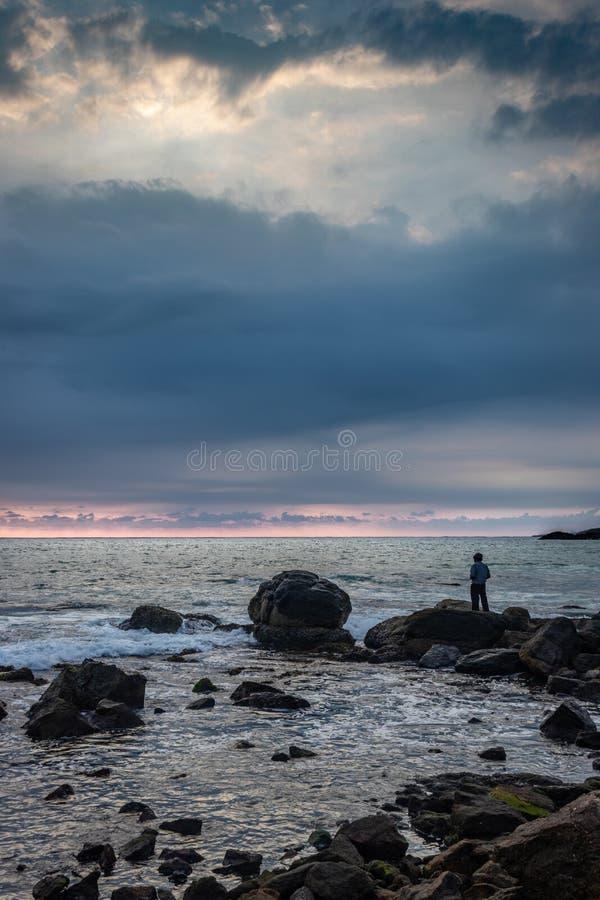 Aufpassender Horizont des Mannes Seevon der Stellung auf Felsen lizenzfreies stockbild