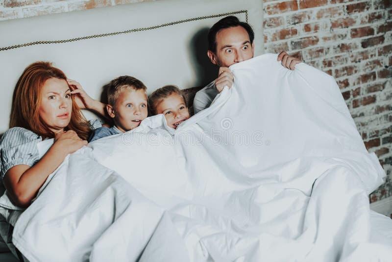Aufpassender Horrorfilm der Familie beim Legen in Bett lizenzfreie stockfotografie