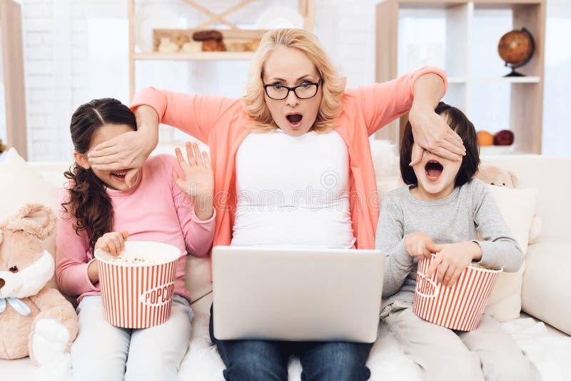 Aufpassender Horrorfilm der schönen älteren Großmutter auf Laptop mit ihren Enkelkindern zusammen stockfotografie