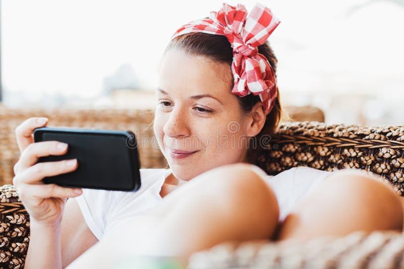 Aufpassender Inhalt der jungen Frau auf ihrem Smartphone lizenzfreie stockfotografie