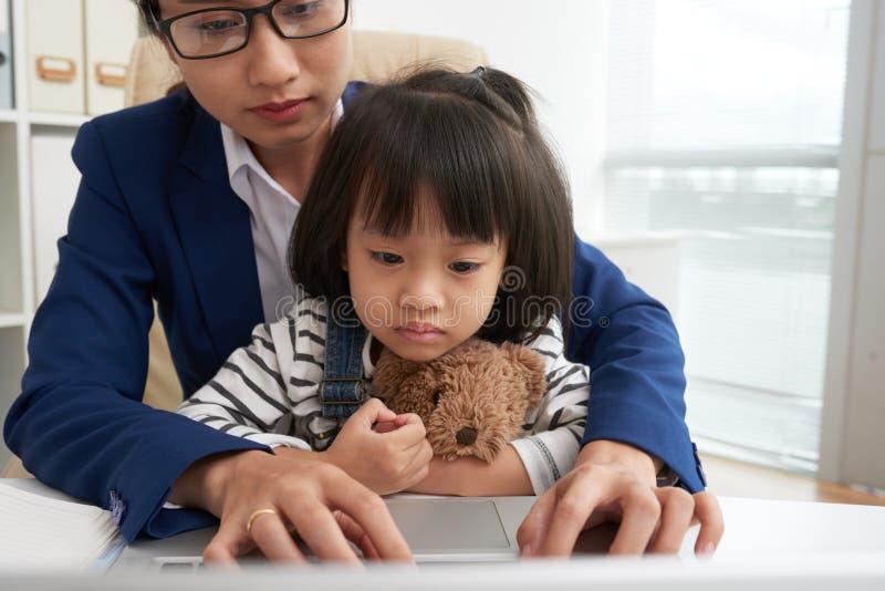 Aufpassender Laptop des reizend Mädchens mit berufstätiger Mutter stockbilder