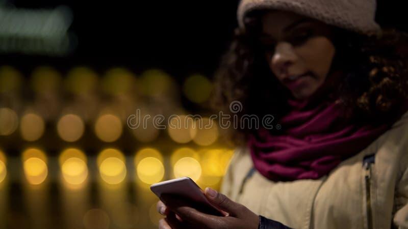 Aufpassender Newsfeed Social Media der jungen Frau und Wartefreunde draußen stockfotografie