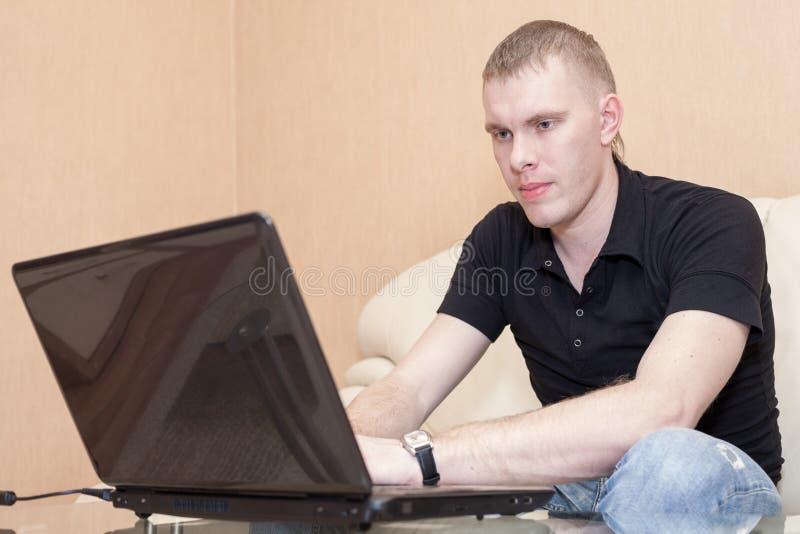 Aufpassender Schirm des hübschen kaukasischen Mannes mit Lächeln auf Gesicht, unter Verwendung des Laptops zu Hause lizenzfreies stockbild