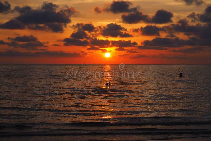 Aufpassender Sonnenuntergang der Leute auf dem Strand Thailand lizenzfreie stockbilder