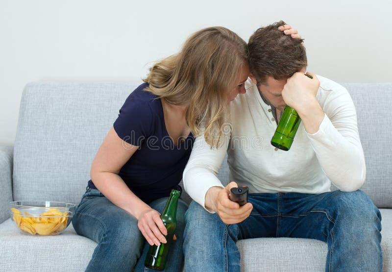 Aufpassender Sport der traurigen Paare lizenzfreie stockbilder