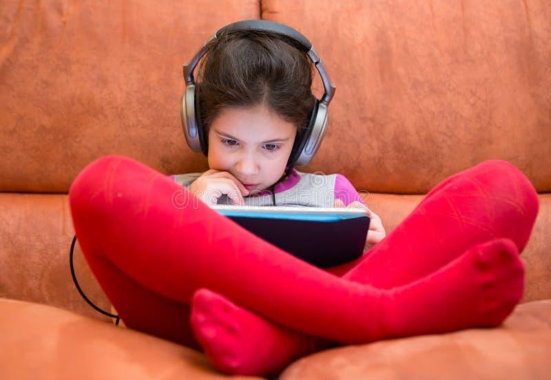 Aufpassender Tabletten-PC des Mädchens mit Kopfhörern stockfoto