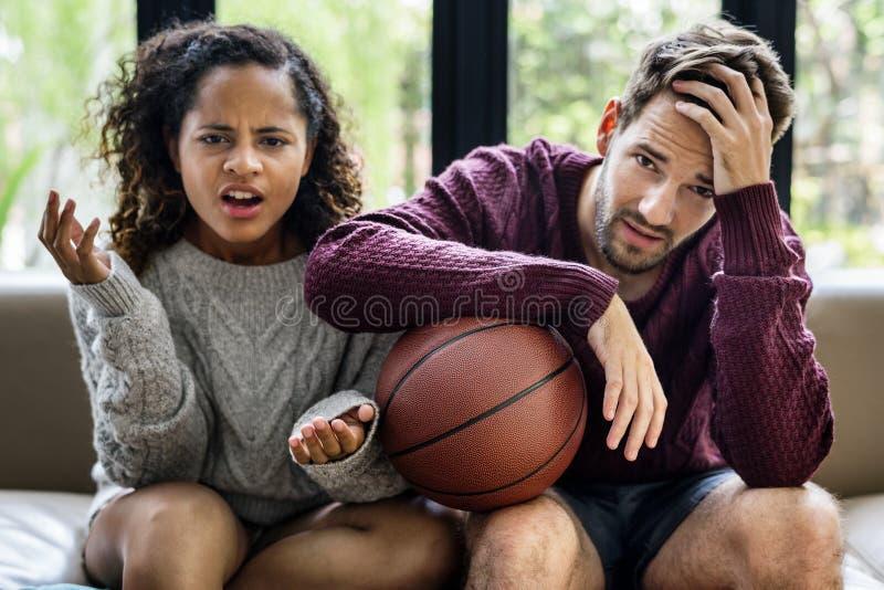 Aufpassendes Basketballspiel der jungen Paare zu Hause stockbilder