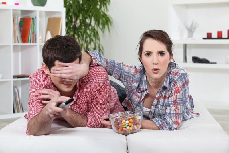 Aufpassendes Fernsehen der jungen Paare lizenzfreie stockfotos