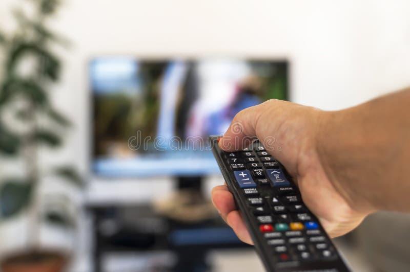 Aufpassendes Fernsehen und Anwendung der Fernbedienung stockbild