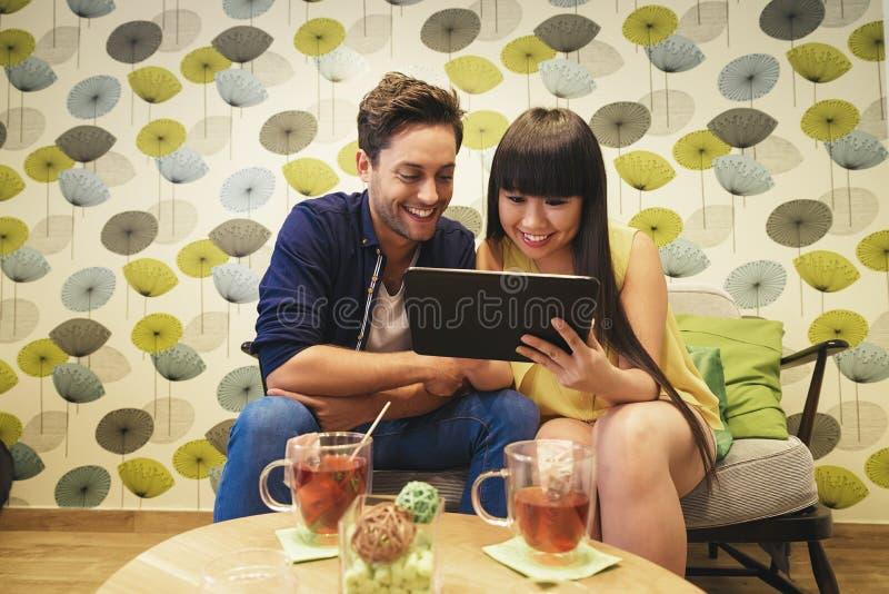 Aufpassendes Social Media des glücklichen Paars in einem Notizbuch an der Stange lizenzfreie stockfotos