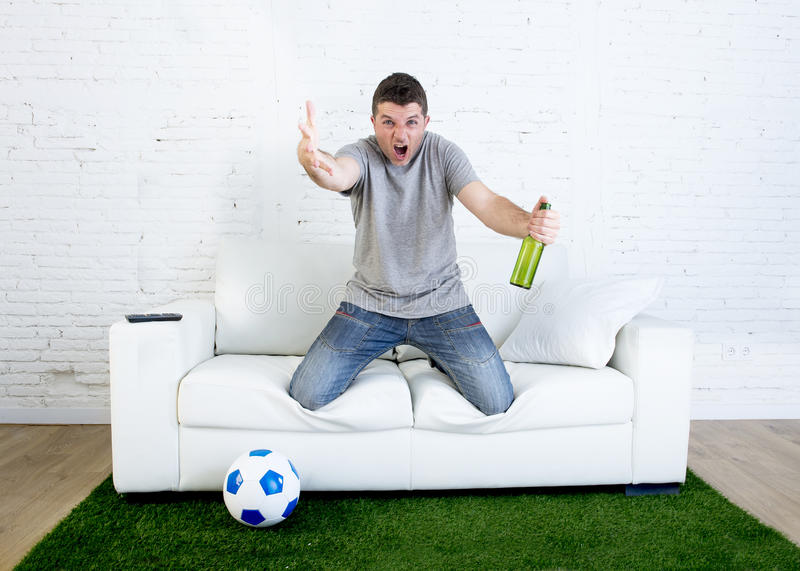 Aufpassendes Spiel des verärgerten Fans des Fußballs fanatischen im dem Fernsehen, welches das Bier gestikuliert Umkippen und die lizenzfreies stockbild