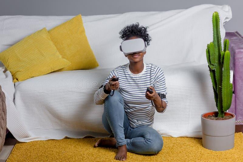 Aufpassendes Video der Afrikanerin unter Verwendung VR-Gläser mit Fernbedienung zu Hause stockbild