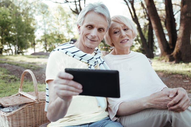 Aufpassendes Video der aufmerksamen Paare auf Tablette lizenzfreie stockfotografie