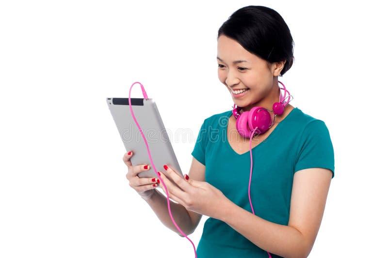 Aufpassendes Video des entzückenden Mädchens auf Tablettengerät lizenzfreie stockbilder