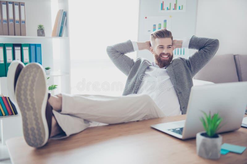 Aufpassendes Video des glücklichen erfüllten Geschäftsmannes auf seinem Laptop während h lizenzfreie stockfotos