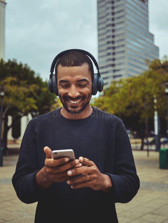 Aufpassendes Video des jungen Mannes unter Verwendung des Handys stockbild