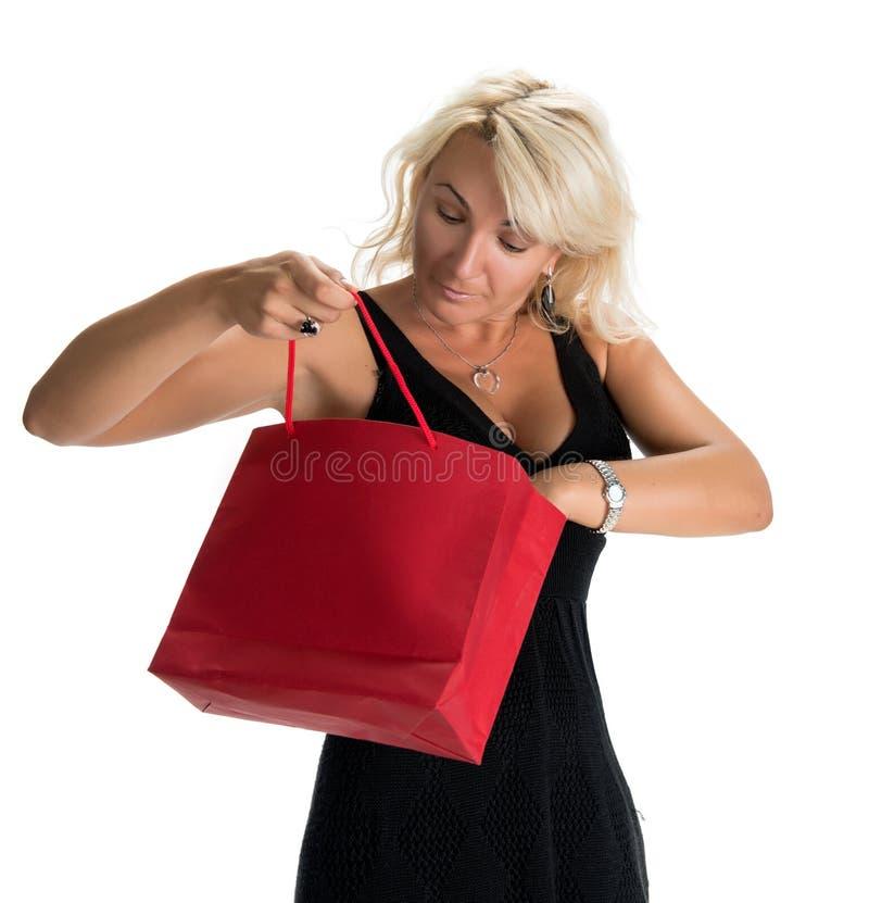 Aufregende Frau, die innere Einkaufstasche schaut stockfotografie