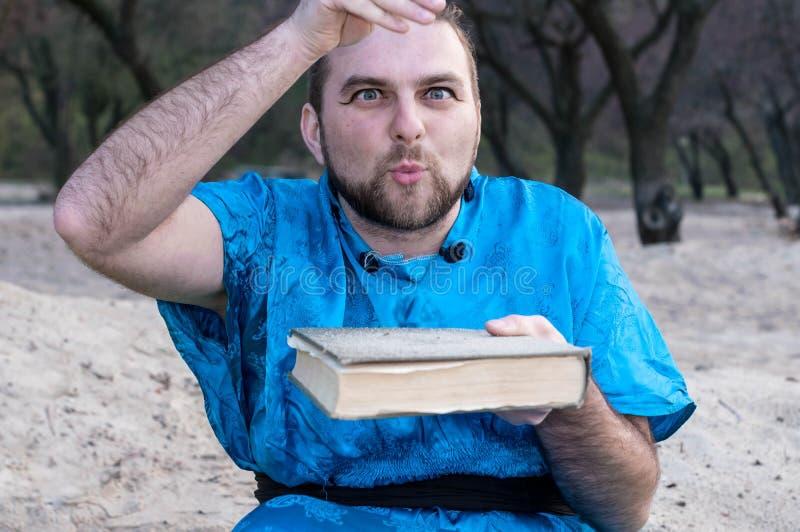 Aufregender gut aussehender Mann in str?mendem Sand des blauen Kimonos auf Buch stockfotos