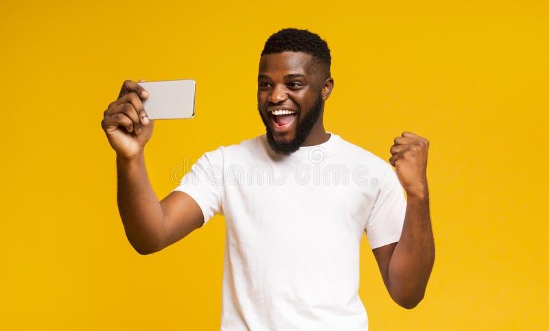 Aufregter afrikanischer Junge feiert Erfolg, mit Smartphone über gelb Hintergrund lizenzfreie stockfotografie