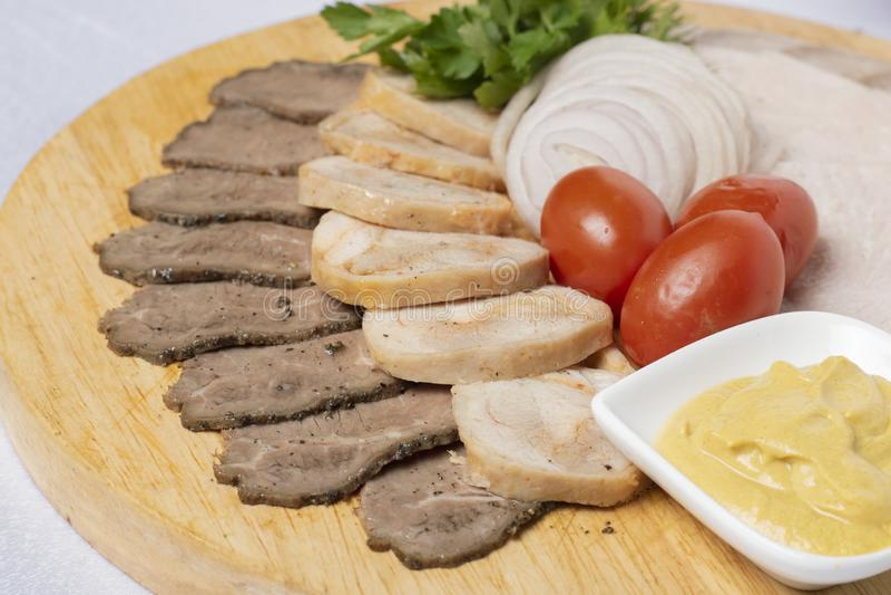 Aufschnitt und sortiertes Fleisch, Käsesoße und Kirschtomaten mit Zwiebelringen stockbild