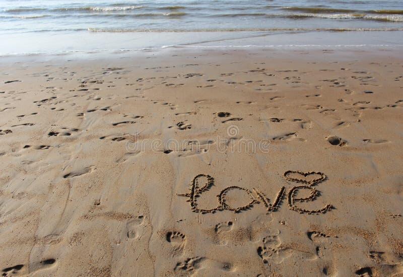 Aufschrift 'der Liebe 'und ein Symbol des Herzens im Sand Abdrücke im Sand und Meereswellen bei Sonnenuntergang stockfotos