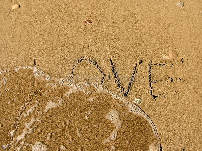 Aufschrift auf dem Strandsand über Liebe lizenzfreies stockbild