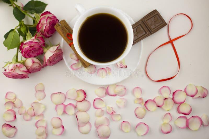 Aufschrift auf März achter von den rosafarbenen Blumenblättern, Kaffee, Zimt, Schokolade auf einer weißen Hintergrundschokolade stockfotos