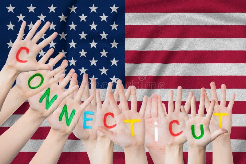 Aufschrift Connecticut auf den Händen der Kinder vor dem hintergrund einer wellenartig bewegenden Flagge der USA stockbild