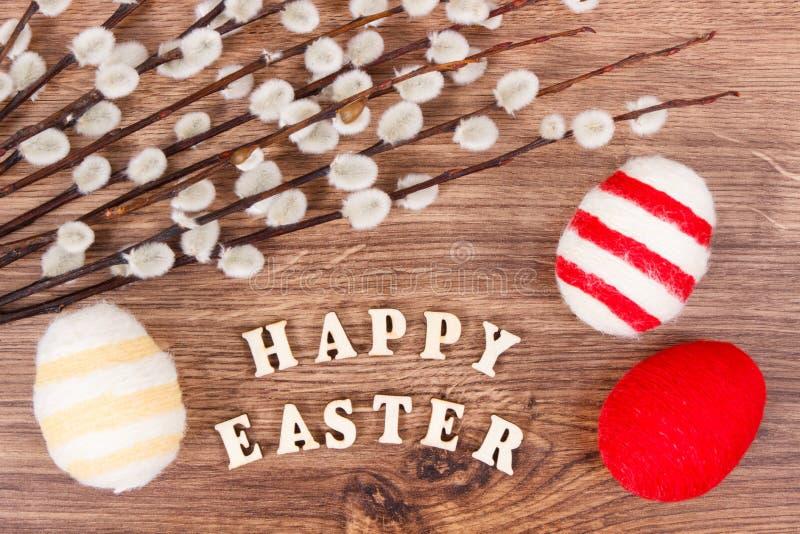 Aufschrift fröhliche Ostern, Zweige der Weide und der bunten Eier wickelte woolen Schnur auf rustikalem Brett ein lizenzfreie stockfotografie
