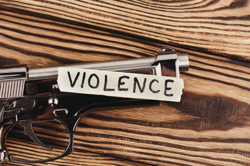 Aufschrift GEWALTTÄTIGKEIT auf heftigem Papier und glatter Pistole stockfoto