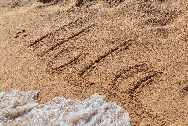 Aufschrift HOLA auf dem Strandsand lizenzfreie stockbilder