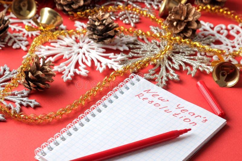 Aufschrift-Jahresvorsatz in einem Notizbuch und verschiedenen Dekorationen des neuen Jahres auf einem roten Hintergrund Neues Jah stockfotografie