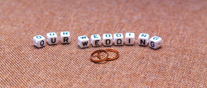 Aufschrift unsere Hochzeit und Eheringe auf braunem Gewebe textur stockbild