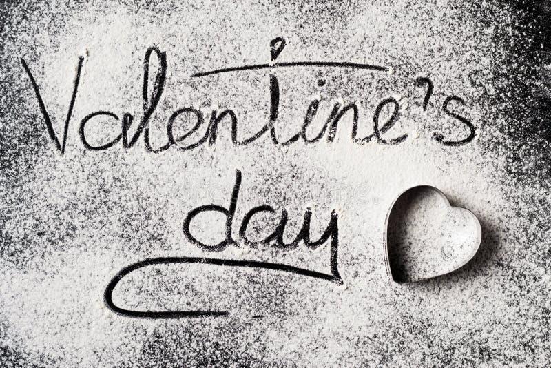 Aufschrift-Valentinsgruß-Tag auf einer Draufsicht des Weizenmehl-Hintergrundes lizenzfreie stockbilder