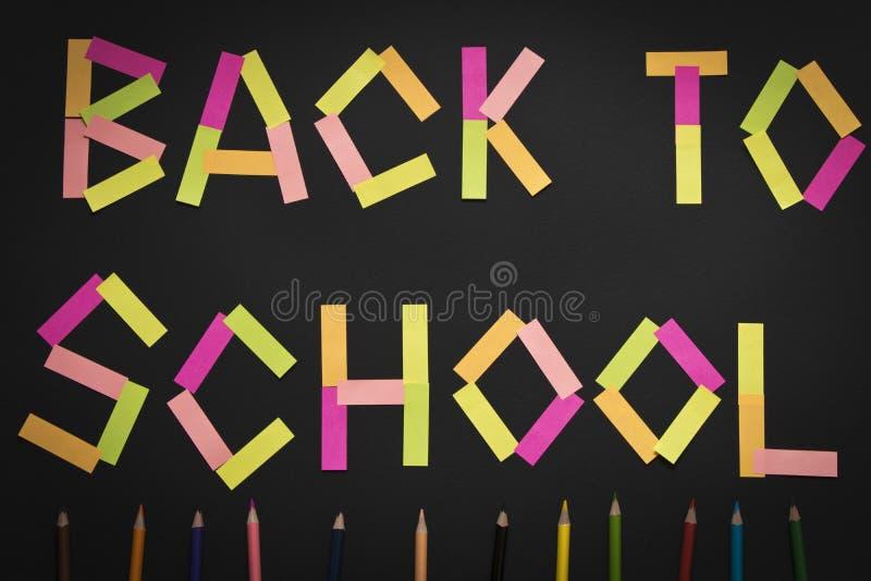 Aufschrift zurück zu Schule von farbigen Aufklebern auf der Tafel mit farbigen Bleistiften stockfotos