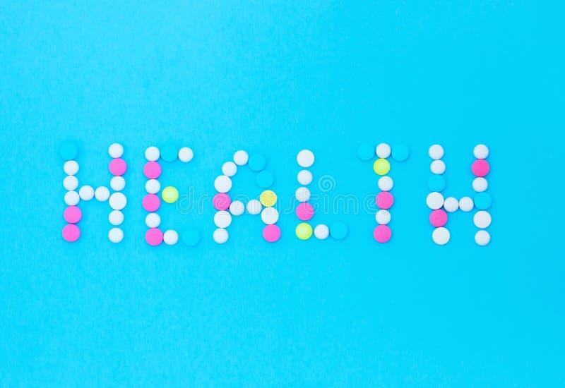Aufschriftgesundheit von den Tabletten auf einem blauen Hintergrund lizenzfreie stockfotografie