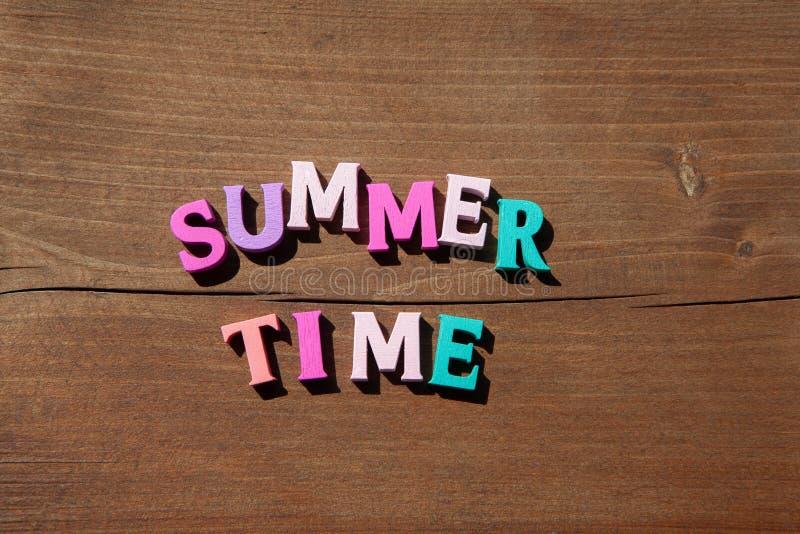 Aufschriftsommerzeit durch mehrfarbige hölzerne Buchstaben auf hölzernem Hintergrund Glückliche Sommerzeit des Konzeptes lizenzfreies stockbild