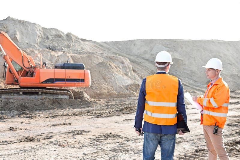Aufsichtskräfte, die an der Baustelle gegen klaren Himmel stehen lizenzfreies stockfoto
