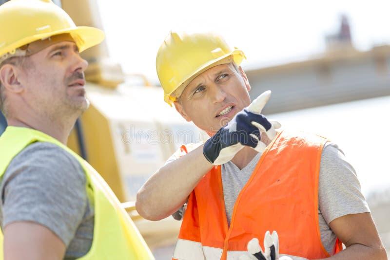 Aufsichtskraft, die dem Kollegen etwas an der Baustelle am sonnigen Tag zeigt stockfoto