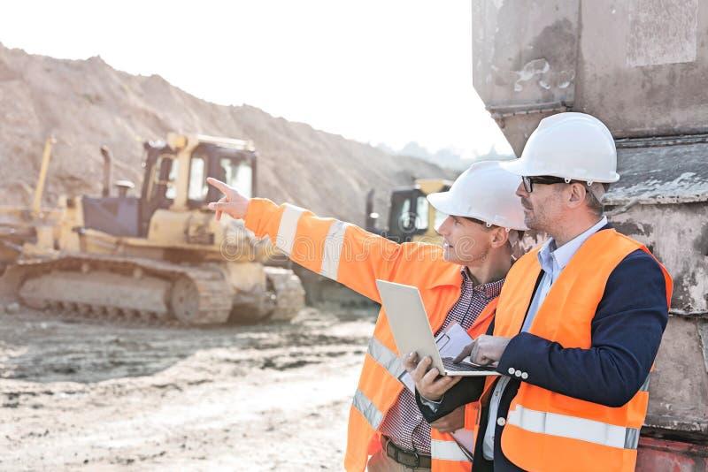 Aufsichtskraft, die dem Mitarbeiter etwas hält Laptop an der Baustelle zeigt lizenzfreie stockfotos