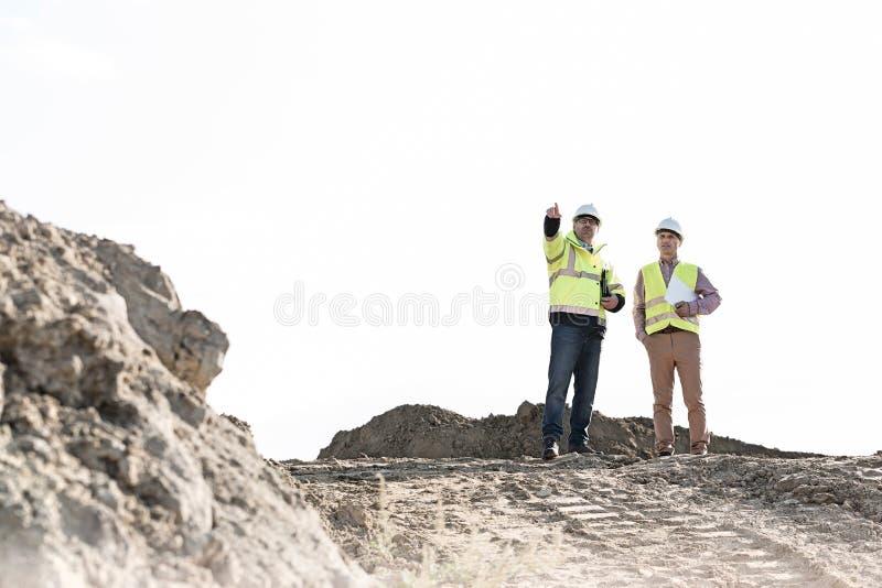 Aufsichtskraft, die mit Kollegen an der Baustelle gegen klaren Himmel sich bespricht lizenzfreie stockfotos