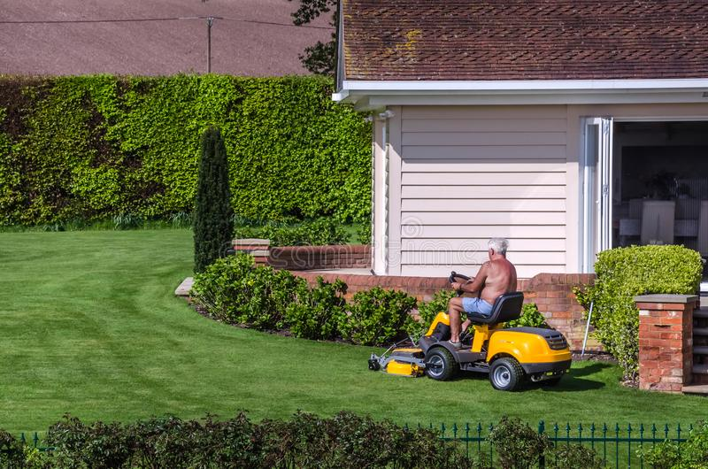Aufsitzmäher des älteren Bürgers in einem Garten stockbild