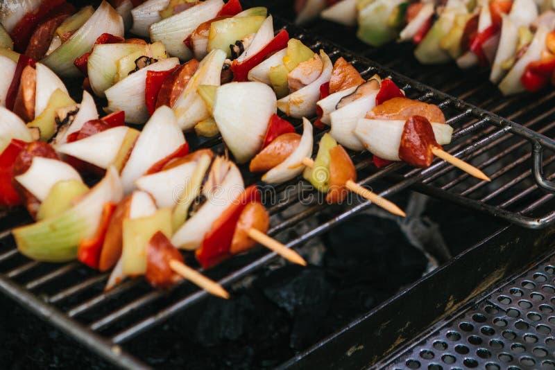 Aufsteckspindeln mit Stücken Würsten, Zwiebeln, Pfeffer werden auf einem Gitter auf Kohlen gekocht Rest und draußen essen stockfotografie
