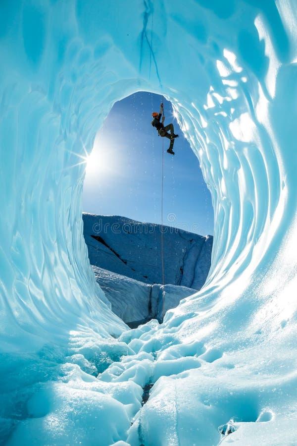 Aufsteigender Eisbergsteiger ein Seil über Eingang der großen blauen Eishöhle auf dem Matanuska-Gletscher in Alaska stockbilder