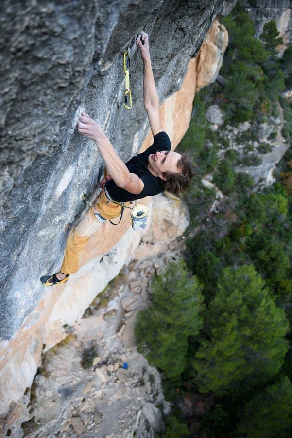 Aufsteigender Kletterer eine schwierige Klippe Extremes Sport climbi stockfoto