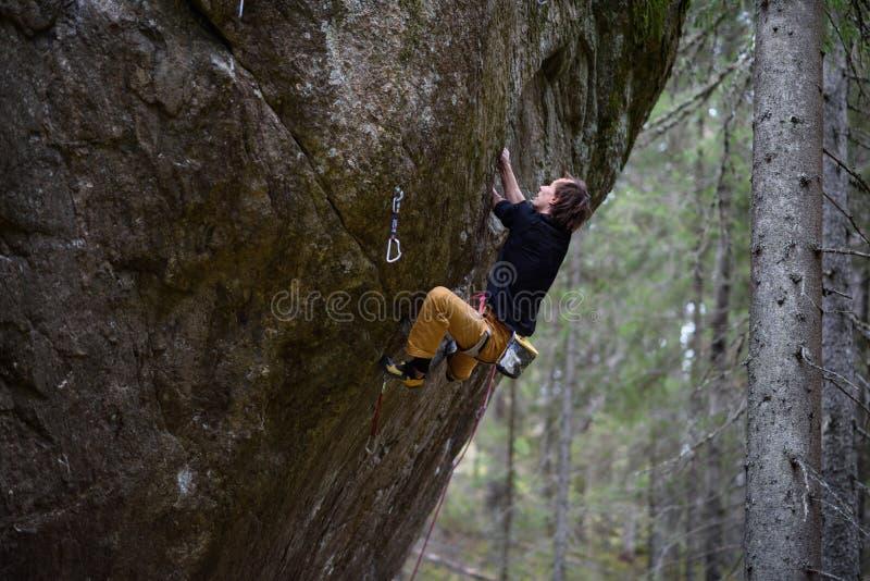 Aufsteigender Kletterer eine schwierige Klippe Extremes Sportklettern Freiheit, Risiko, Herausforderung, Erfolg stockfoto