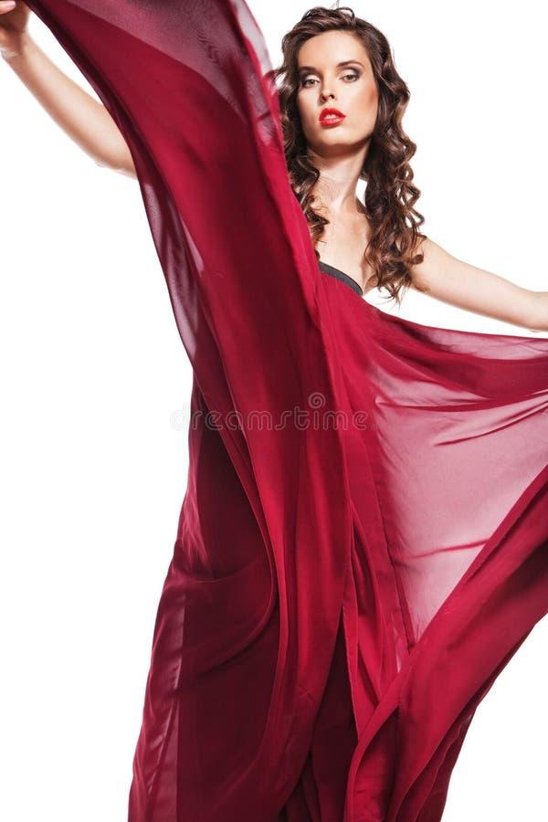 Aufstellung der Frau im roten Kleiderflugwesen auf Wind lizenzfreie stockfotos