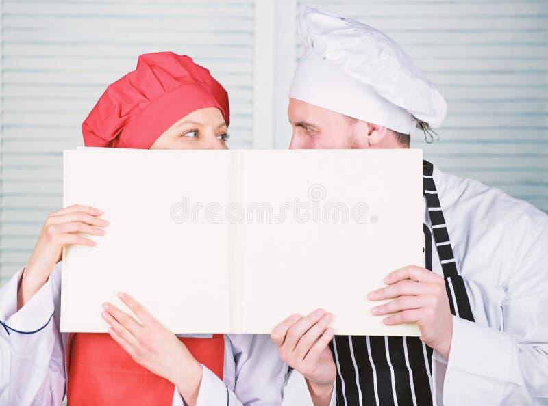 Aufstellung der Handelsbilanz im Restaurant Chef und Vorbereitungskoch, der leeres Kontoblatt h?lt Vorlagenausf?hrungsbuch des ko stockfoto