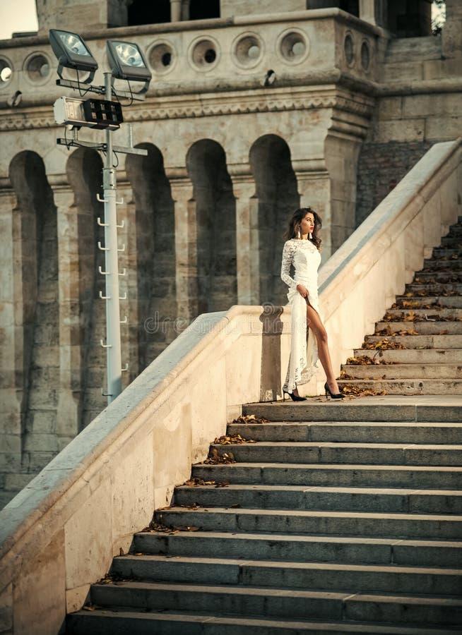 Aufstellung der modernen Frau Junge Frau im weißen langen Kleid Treppenhaus steigernd stockfoto