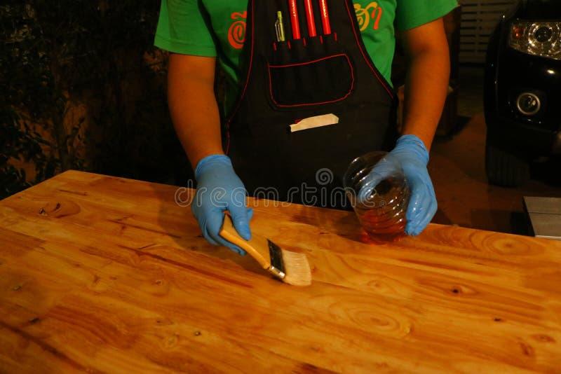 Auftragen des Lacks auf eine Holzoberfläche mit einer Bürste lizenzfreies stockbild